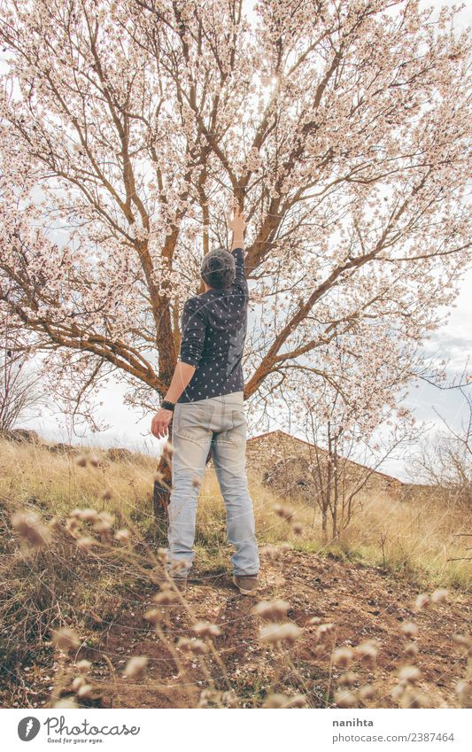 Young man touching a tree in bloom Lifestyle Style Wellness Senses Human being Masculine Youth (Young adults) Man Adults 1 30 - 45 years Environment Nature