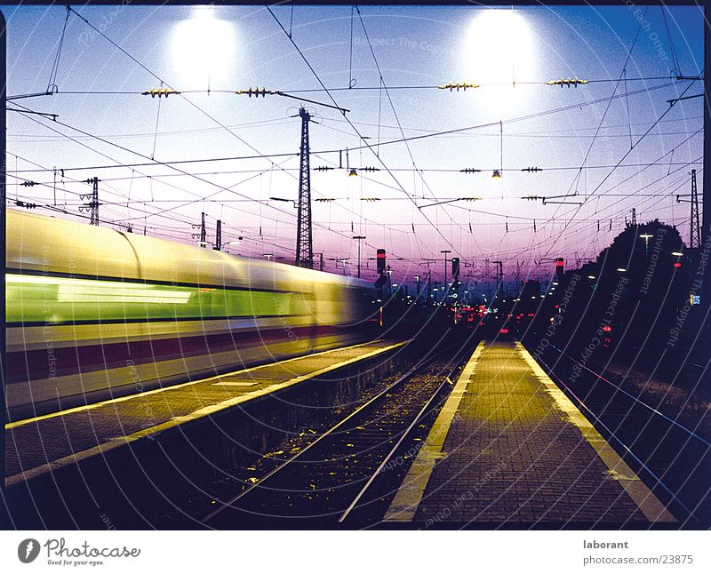 ice in the evening Express train Railroad Railroad tracks Overhead line Electricity Engines Speed Wanderlust Transport Train station Dusk Cable