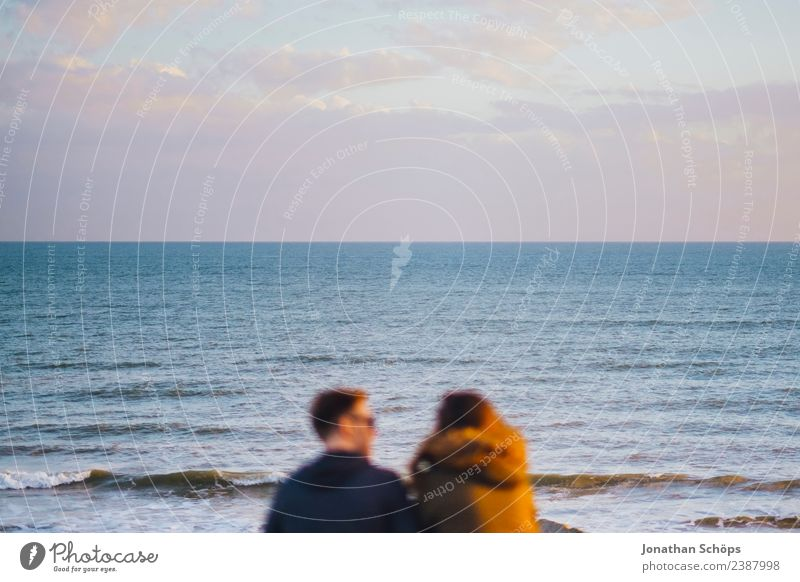 Couple sits by the sea Partner 2 Human being Sky Sunrise Sunset Waves Coast Brighton Great Britain Europe Touch Smiling To talk Esthetic Together Happy