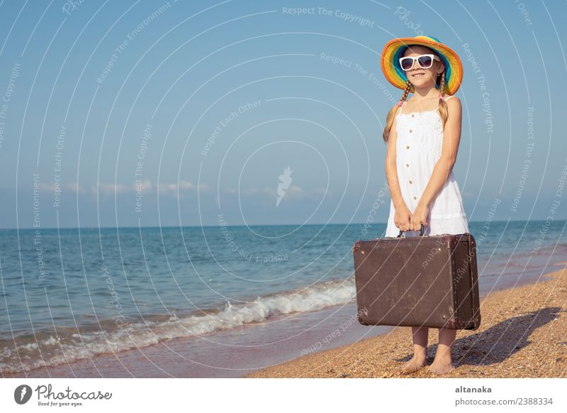 One happy little girl with suitcase standing on the beach. Woman Child Human being Nature Vacation & Travel Summer Sun Ocean Relaxation Joy Beach Street Adults