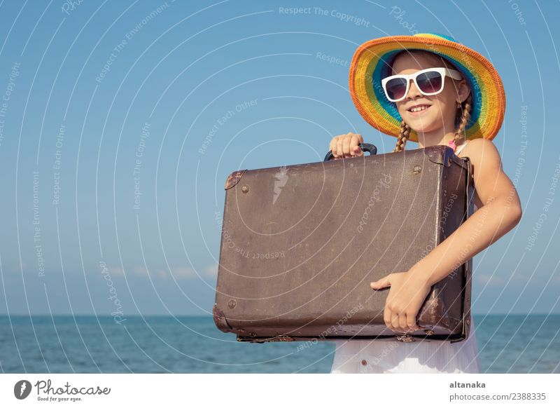 One happy little girl with suitcase standing on the beach. Woman Child Human being Sky Nature Vacation & Travel Summer Sun Ocean Relaxation Joy Beach Adults