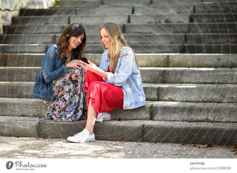 Two young women looking at an smart phone outdoors Lifestyle Shopping Joy Happy Beautiful Telephone PDA Technology Human being Feminine Young woman
