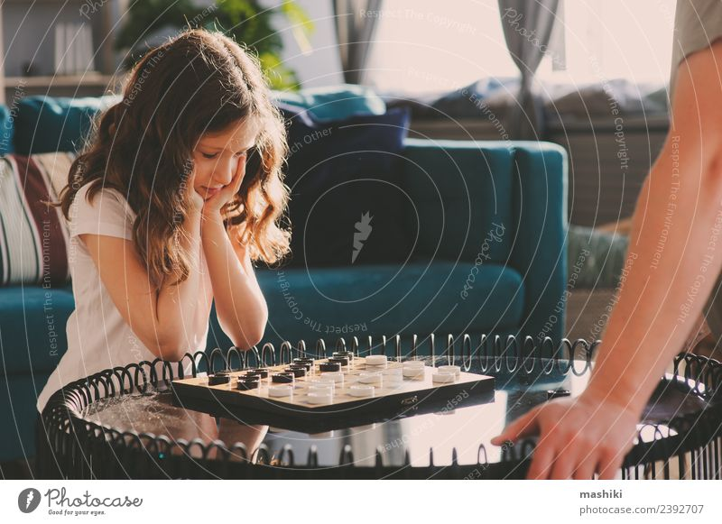 child girl playing checkers with her dad Lifestyle Leisure and hobbies Playing Chess Success Child Parents Adults Father Family & Relations Infancy Toys Think