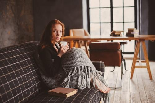 young sick woman healing at home Tea Lifestyle Illness Relaxation Winter Woman Adults Autumn Warmth Sweater Red-haired Wood Metal Dream Modern Pain Considerate