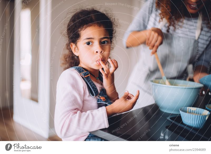 little african girl is licking dough from fingers Dessert Joy Happy Beautiful Kitchen Child Human being Woman Adults Mother Infancy Fingers Together Small