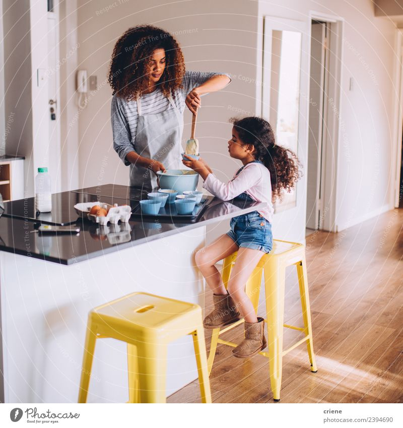 little african girl is helping her mum preparing cupcake dough Dough Baked goods Dessert Joy Happy Beautiful Kitchen Child School Human being Woman Adults