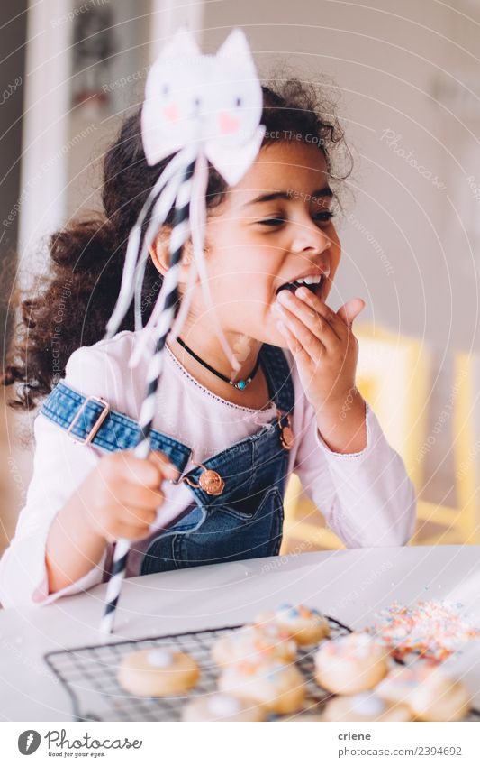 african little girl is eating selfmade cookies at home Dessert Lifestyle Joy Happy Beautiful Table Kitchen Child Human being Woman Adults Infancy Smiling