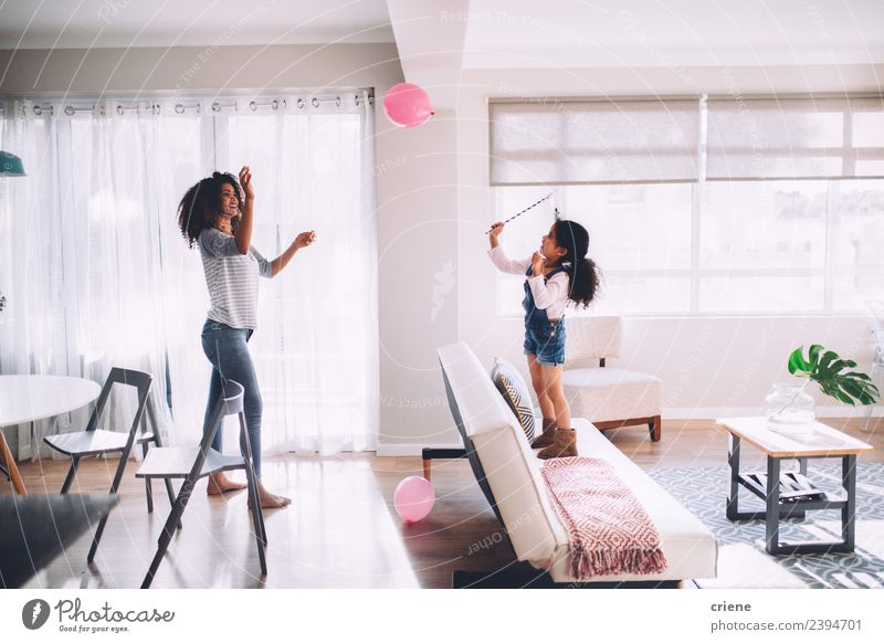 african mother and daughter playing with balloon in living room Happy Decoration Child Woman Adults Mother Family & Relations Infancy Smiling Happiness Cute