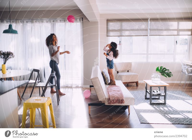 african mother and daughter playing with balloon in living room Happy Playing Decoration Living room Child Woman Adults Mother Family & Relations Infancy