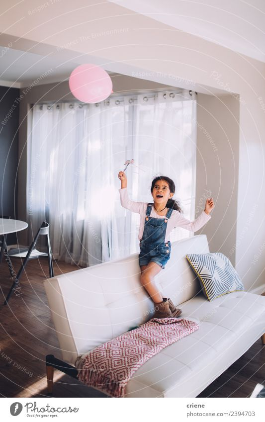 African happy girl playing with a balloon on couch Child Beautiful Joy Happy Small Playing Infancy Smiling Happiness Cute Balloon Couch Beauty Photography Home