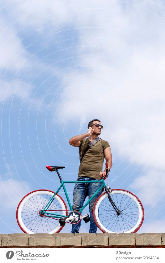 Young man standing outdoors and calling on the phone Lifestyle Style Vacation & Travel Cycling Business To talk Telephone Technology Human being Masculine