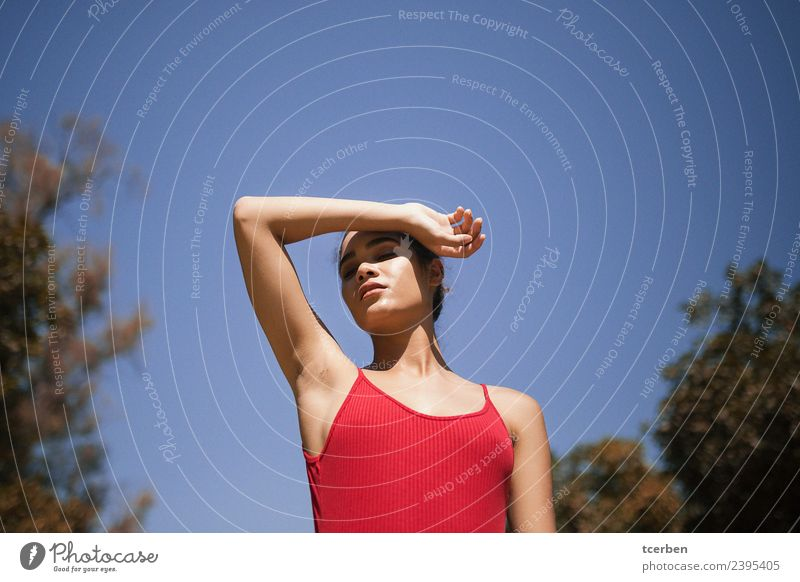 Portrait of a woman in the sun covering her face with her arm Sky Youth (Young adults) Blue Colour Beautiful Sun Red Relaxation Loneliness Calm 18 - 30 years