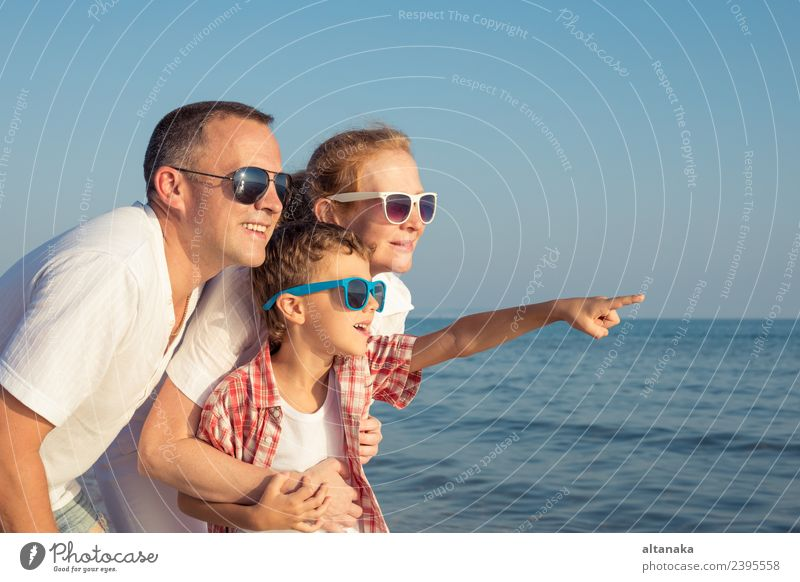 Happy family standing on the beach at the day time. Woman Child Human being Vacation & Travel Man Summer Ocean Relaxation Joy Beach Adults Lifestyle Love Sports