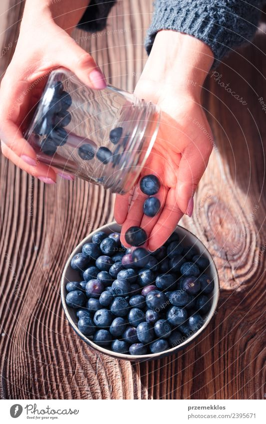 Woman putting fresh blueberries from a jar into a small bowl Nature Blue Summer Hand Adults Natural Wood Food Above Fruit Nutrition Vantage point Fresh