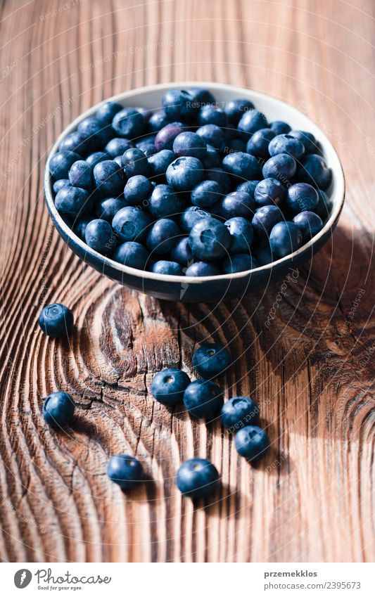 Freshly gathered blueberries put into ceramic bowl Food Fruit Nutrition Organic produce Vegetarian diet Diet Bowl Summer Table Nature Wood Authentic Delicious
