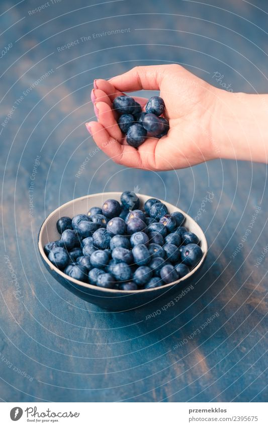 Woman putting fresh blueberries from a jar into a small bowl Nature Blue Summer Hand Adults Natural Food Fruit Nutrition Fresh Table Delicious Harvest