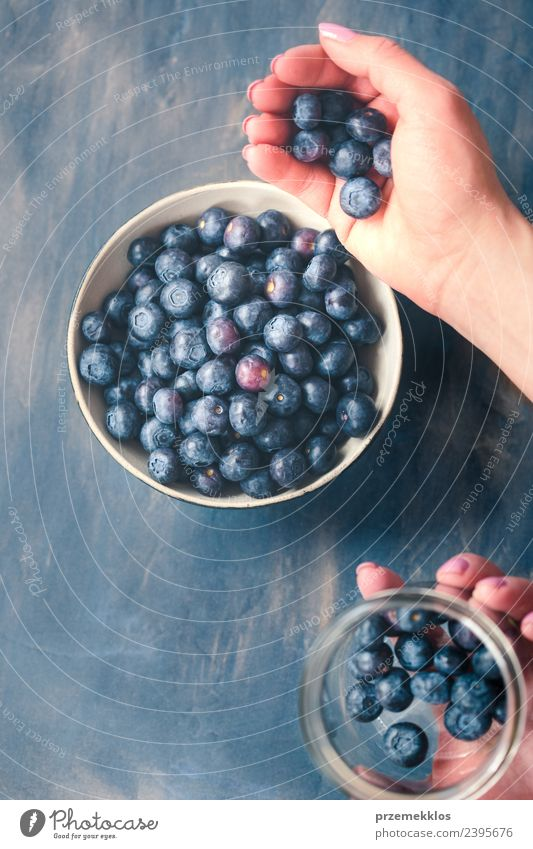 Woman putting fresh blueberries from a jar into a small bowl Nature Blue Summer Hand Adults Natural Wood Food Above Fruit Nutrition Vantage point Fresh Table