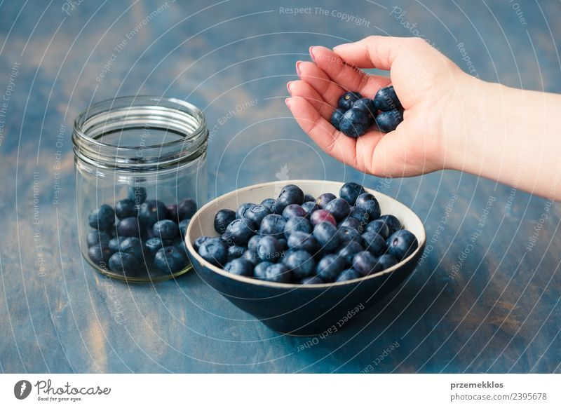 Woman putting fresh blueberries from a jar into a small bowl Nature Blue Summer Hand Adults Natural Wood Fruit Nutrition Fresh Table Delicious Harvest Mature
