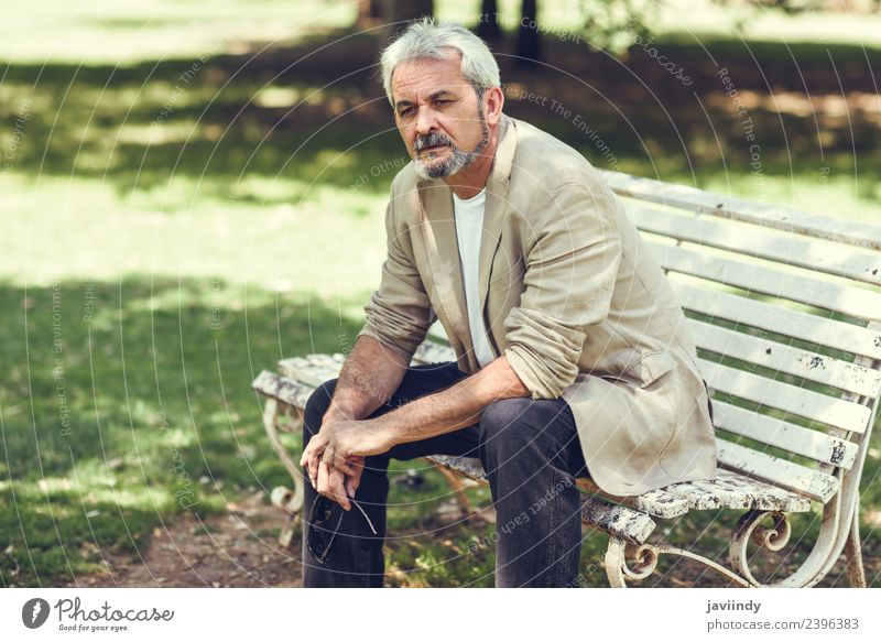 Pensive mature man sitting on a bench in an urban park. Lifestyle Happy Retirement Human being Masculine Man Adults Male senior Senior citizen 1 45 - 60 years