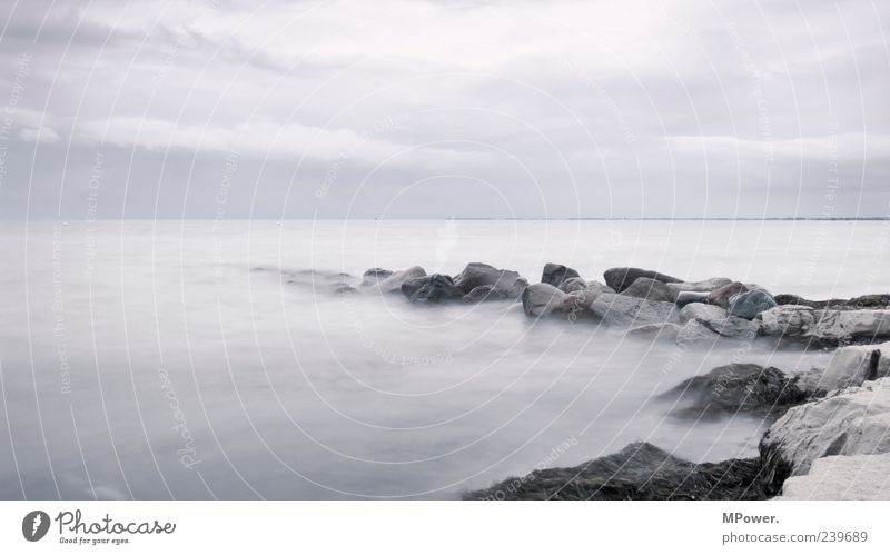Fehmarn Baltic Sea Ocean Water Stone Sand Horizon Gray Gloomy Colorless Deserted Fog Bad weather Long exposure Waves Clouds Coast Lakeside Beach Rain Rock