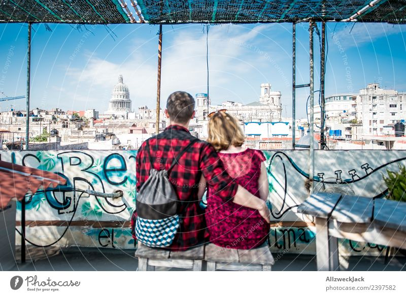 Couple sitting on a roof overlooking the Capitol in Havana Cuba United States Capitol Skyline Vantage point Apartment Building Tower block Blue sky
