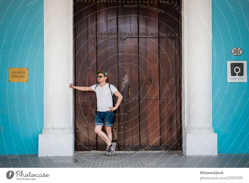 young man waits at a wooden door and supports himself Cuba Havana Island Vacation & Travel Travel photography Trip Sightseeing Street Town Blue Wanderlust Day