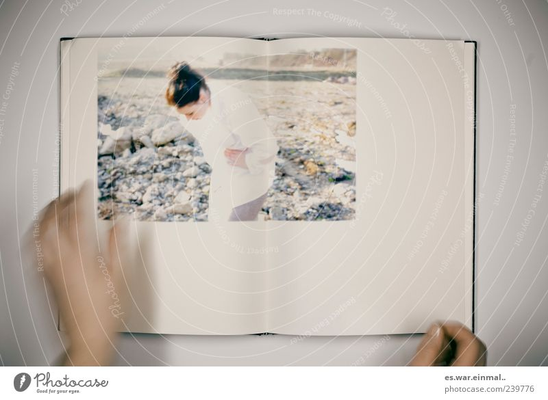Picture in picture Feminine Hand 1 Human being Rock Shirt Discover Reading Stand Book To leaf (through a book) Picture book Motion blur Looking Art Colour photo