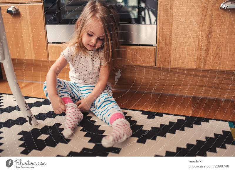 cute toddler girl put on socks at home Breakfast Lifestyle Joy Happy Beautiful Playing Kitchen Child Baby Woman Adults Infancy Clothing Sit Happiness Small