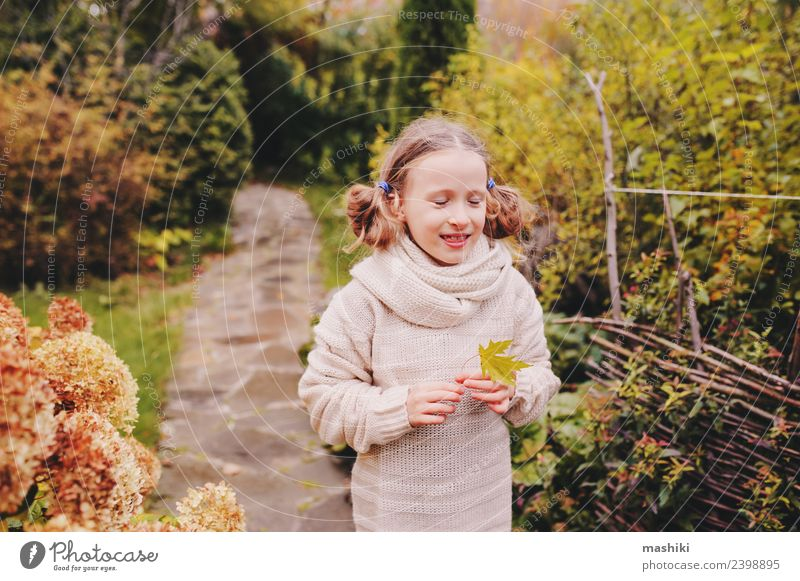 kid girl walking in the autumn garden Lifestyle Joy Vacation & Travel Garden Child Work and employment Nature Autumn Flower Leaf Lanes & trails Sweater Scarf