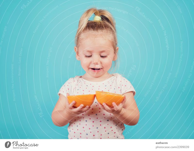 smiling baby with an orange on blue background Child Human being Joy Girl Eating Lifestyle Healthy Feminine Laughter Food Fruit Nutrition Orange Infancy Smiling