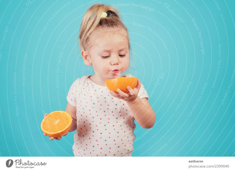 baby eating an orange on blue background Food Fruit Orange Nutrition Eating Breakfast Lunch Human being Feminine Baby Girl Infancy 1 3 - 8 years Child Diet