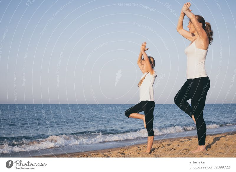 Mother and daughter doing yoga exercises on the beach. Woman Child Human being Nature Summer Relaxation Joy Beach Adults Lifestyle Sports Family & Relations