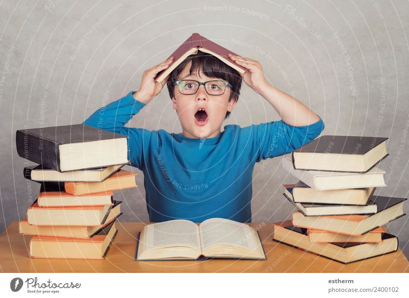 surprised boy with books on a table Lifestyle Joy Reading Human being Masculine Child Toddler Infancy 1 8 - 13 years Culture Movement Think To hold on Fitness