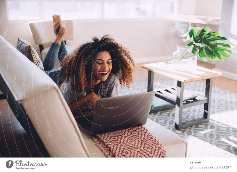 happy african woman lying on couch while using her laptop Lifestyle Happy Beautiful House (Residential Structure) Decoration Sofa Work and employment Computer
