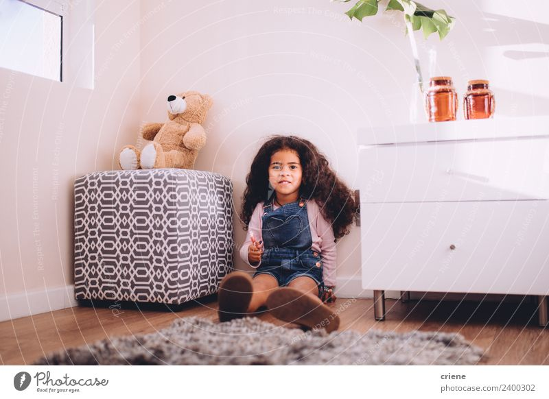 little afrcian girl is holding a lollipop sitting on the floor Happy Beautiful Child Plant Boots Toys Teddy bear Smiling Sit Small Cute Bear Home room kid