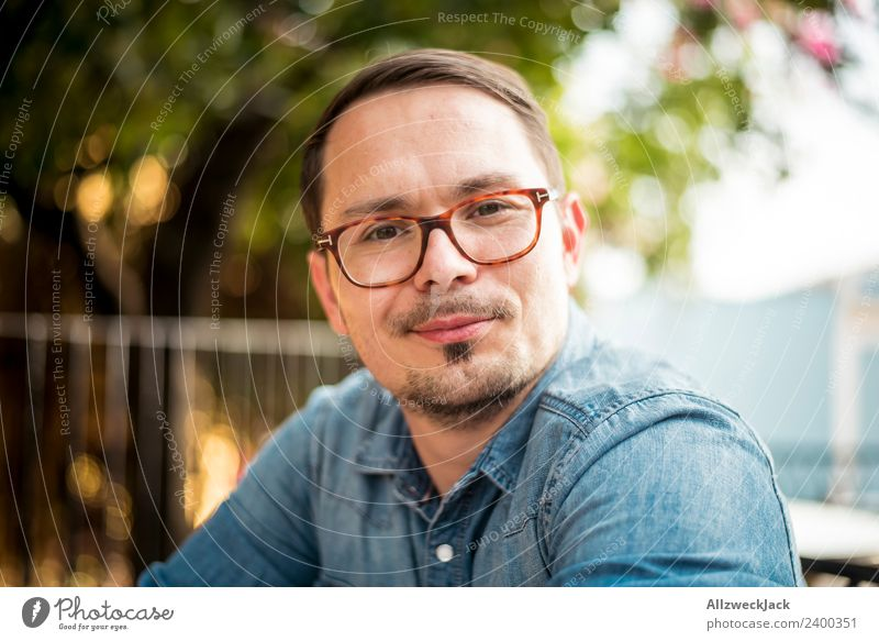 Portrait of a young man with glasses Day Exterior shot Portrait photograph 1 Person Young man Person wearing glasses Eyeglasses Facial hair Moustache