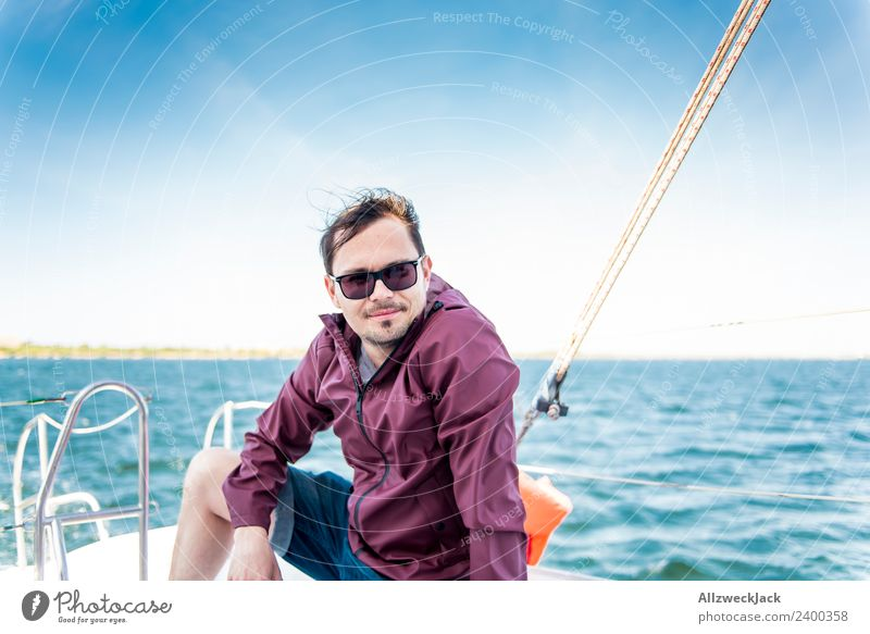 young man sits on a sailboat on the sea Day 1 Person Portrait photograph Young man Short haircut Sunglasses Water Ocean Sailing Sailboat Maritime Lake Blue sky