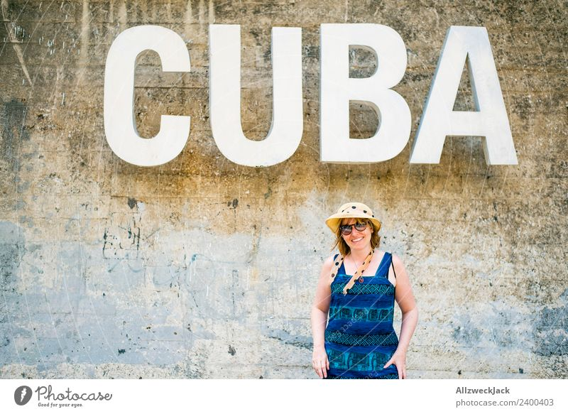Woman with blue dress and hat before the word CUBA Day Feminine 1 Person Young woman Wall (barrier) Wall (building) Cuba Letters (alphabet) Typography Word