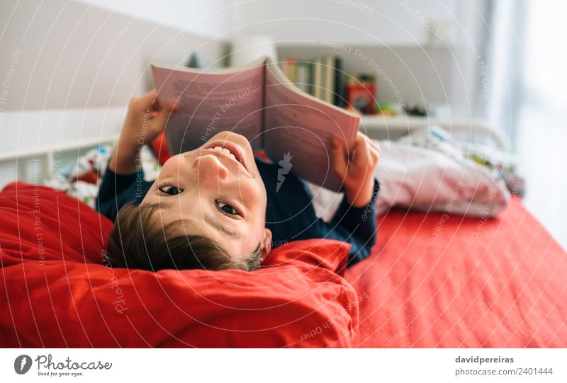 Boy looking camera while reading a book Lifestyle Joy Happy Beautiful Calm Leisure and hobbies Reading Bedroom Child Human being Boy (child) Man Adults Culture