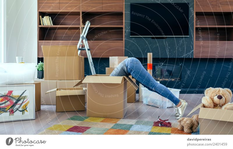Woman inside a box preparing the move Lifestyle House (Residential Structure) Moving (to change residence) Living room Human being Adults Jeans Sneakers Toys