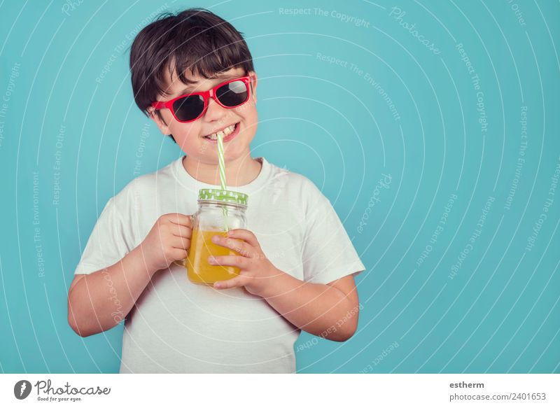 happy boy drinking orange juice on blue background Nutrition Beverage Drinking Lemonade Juice Lifestyle Joy Human being Masculine Child Toddler Infancy 1