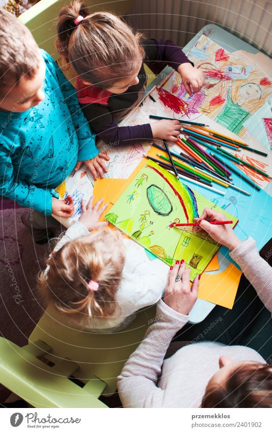 Mom with her little children drawing the pictures Lifestyle Joy Happy Handcrafts Table Children's room Parenting Education Kindergarten School Human being Girl
