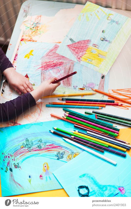 Crayons scattered on desktop filled with colorful drawings Lifestyle Joy Happy Handcrafts Table Education Kindergarten Child School Girl 1 Human being