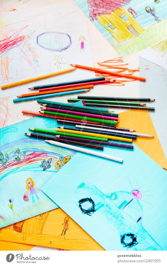 crayons scattered on desktop filled with colorful drawings a