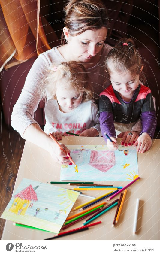 Mom with little girls drawing a colorful picture Lifestyle Joy Happy Handcrafts Table Parenting Education Kindergarten Child School Human being Girl Parents