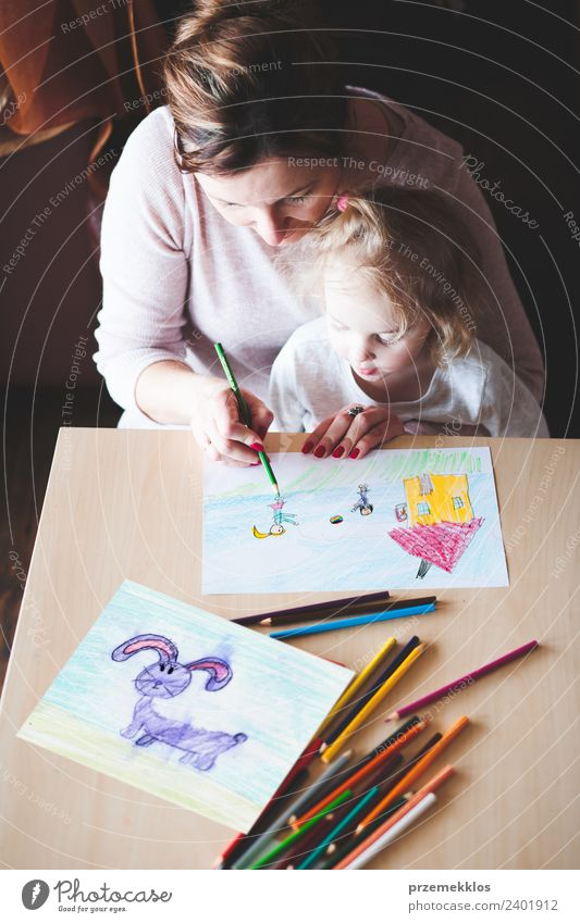 Mom with little daughter drawing a colorful picture Lifestyle Joy Happy Handcrafts Table Parenting Education Kindergarten Child School Craft (trade) Human being