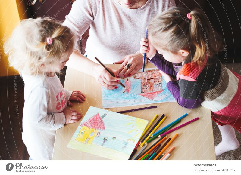 Mom with little girls drawing a colourful pictures of house and playing children using pencil crayons standing at table indoors Lifestyle Joy Happy Handcrafts