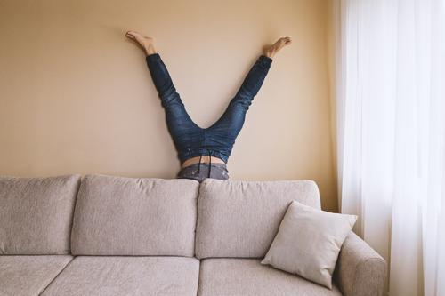 Adult man is standing on his head behind sofa in the room Lifestyle Health care Alternative medicine Athletic Fitness Leisure and hobbies Flat (apartment) Sofa