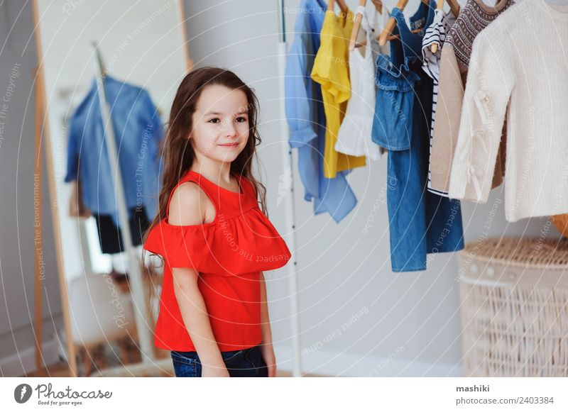 cute little child girl choosing new clothes Shopping Style Child Fashion Clothing Dress Collection Smiling Bright Hip & trendy Small Modern New Red Colour kid