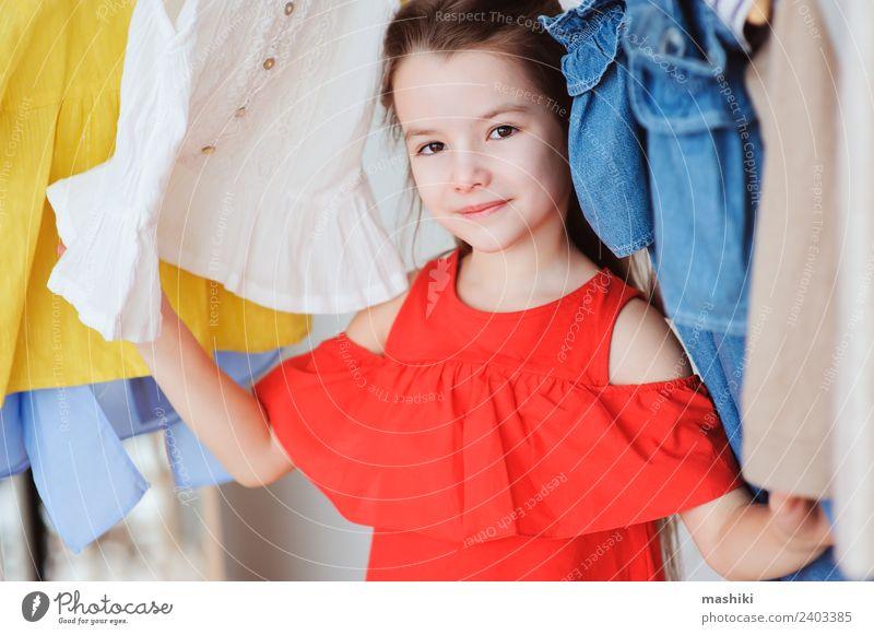 cute little child girl choosing new clothes Shopping Style Child Fashion Clothing Dress Collection Smiling Bright Hip & trendy Modern New Colour kid outfit many